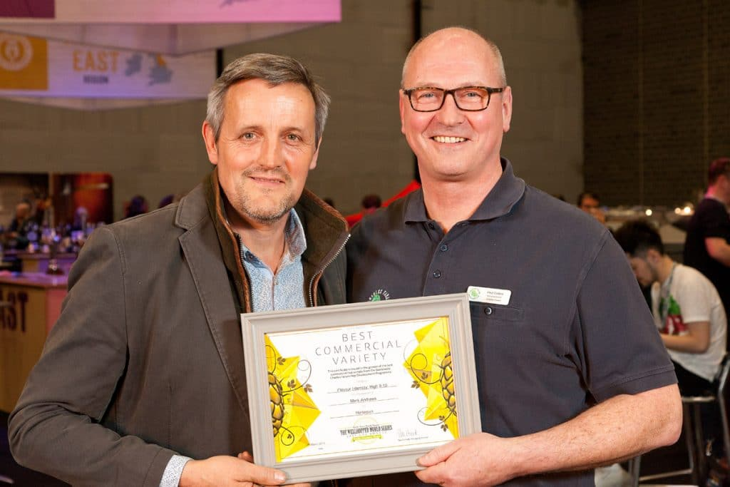Photo of Mark Andrews of Townend Farm accepting his overall winner trophy and certificate from Paul Corbett, Charles Faram Managing Director, for the Wellhopped World Series 2019